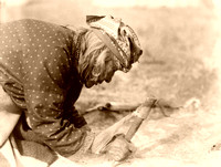 Blackfoot fleshing a hide